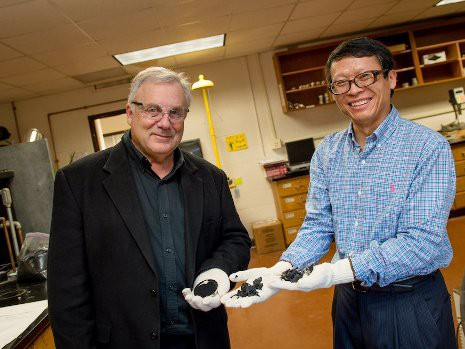 David Hand, left, and Zhanping You hold samples of crumb rubber and chunks of rubber made from recycled tires. They are leading studies to help determine if asphalt made with crumb rubber could be used on Michigan roads. Sara Bird photo / Michigan Technological University