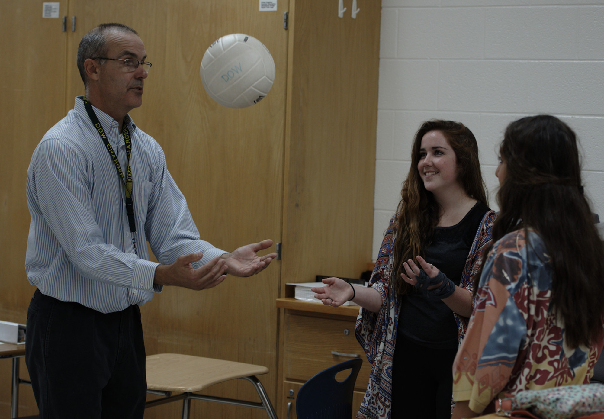 Dow High teacher Thomas McNamara (left) uses a volleyball and motion sensor to map the kinematics of tossing the ball into the air as students Ellen Lavigne (center) and Stephanie Carras (right) observe. A similar process is used to map the kinematics of the solar cars. Saginaw Valley State University photo.