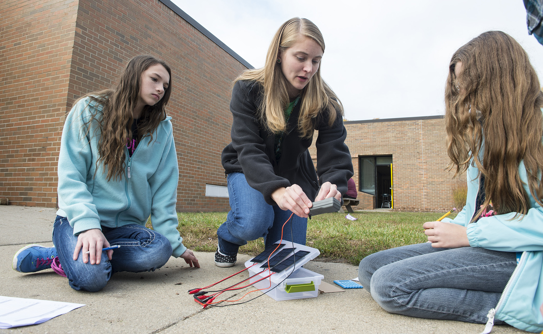 In this photo, Bullock Creek Middle School teacher Ashley Meyer (center) shows students Tiana Lowery (left) and Veronica Card how to measure the energy generated by solar panels.