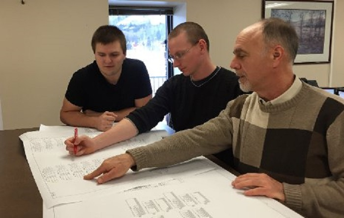 From the left, Troy Johnston and Bob Elsey, interns at Systems Control's Houghton office, work with Tech alumnus John Zipp, senior protection and control engineer, on a schematic for a bus differential panel to be incorporated into an electrical transmission sub-station control house. Michigan Technological University photo.